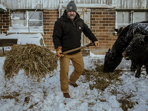 Man working on farm wearing Carhartt hats and clothes
